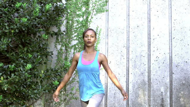 Black woman doing yoga exercise  outdoors, crescent lunge