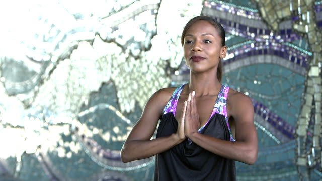 Black woman doing yoga exercises outdoors