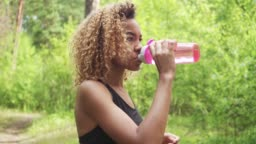 Black woman drinking from pink bottle. Portrait of black young woman taking break while jogging