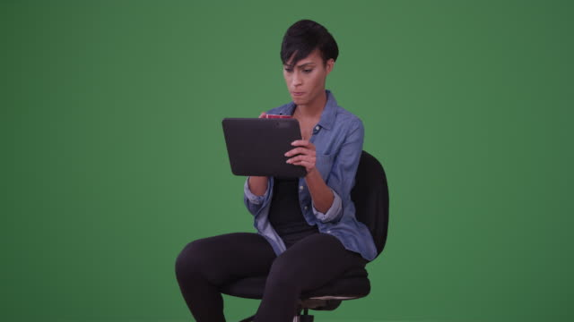 Black woman drinks coffee and reads on her pad on green screen