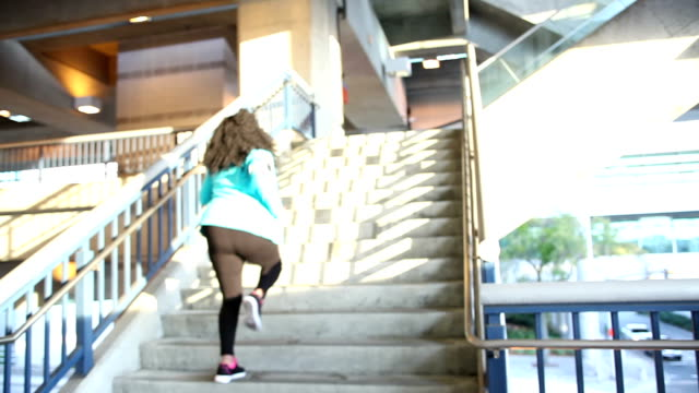 Black woman exercising in city, running up stairs