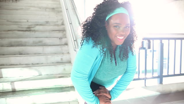 Black woman exercising in city, stretching