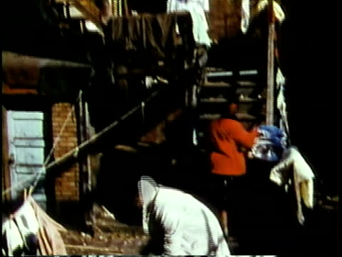 stockvideo's en b-roll-footage met 1963 montage black woman hanging laundry and boys playing in slum area / chicago, united states / audio - chicago illinois