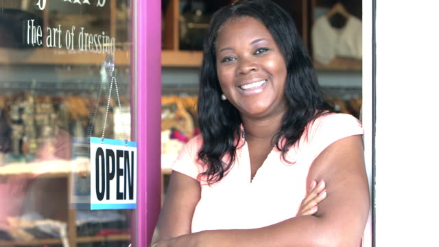 Black woman hanging OPEN sign on door of clothing store