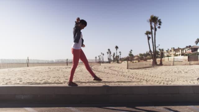 vídeos de stock, filmes e b-roll de black woman having fun balancing on short wall at beach smiling - wide