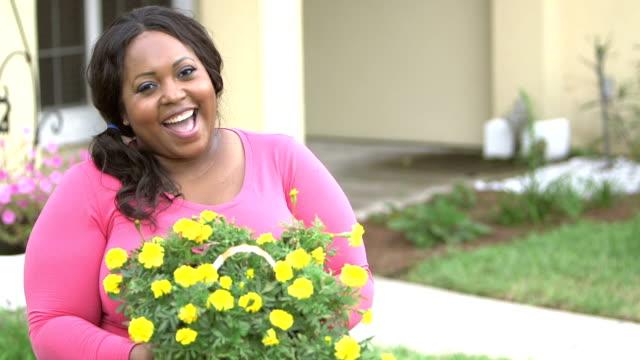 Femme noire à l'arrière yard comptable bac de fleurs jaunes