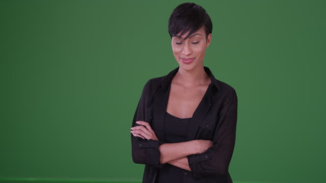 Black woman in black casual wear cracks a smile at the camera on green screen