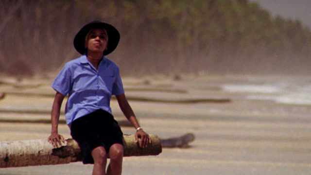 black woman in hat sitting + bouncing on tree limb on beach - tre quarti video stock e b–roll