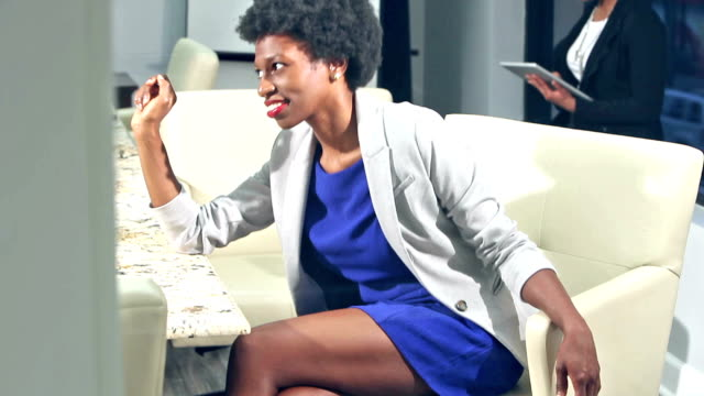 Black woman in office boardroom talking to someone