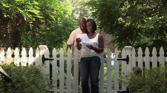 black woman opening mail next to garden gate, husband approaching - 夫点の映像素材/bロール