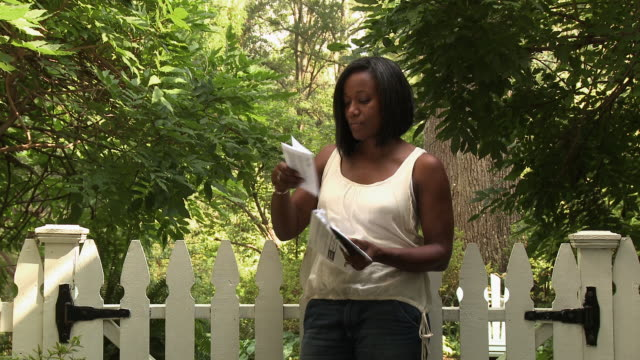 black woman opening mail next to garden gate - reading mail stock videos & royalty-free footage