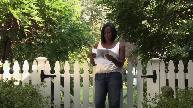 black woman opening mail next to garden gate, worried husband approaching - letter stock videos & royalty-free footage