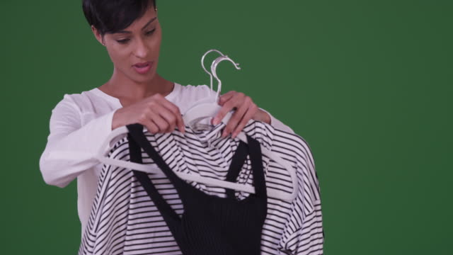 black woman picking out an outfit on green screen - all shirts stock videos & royalty-free footage