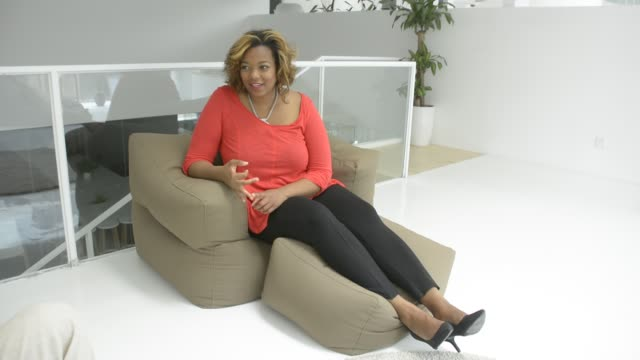 black woman talking to friends on sofa