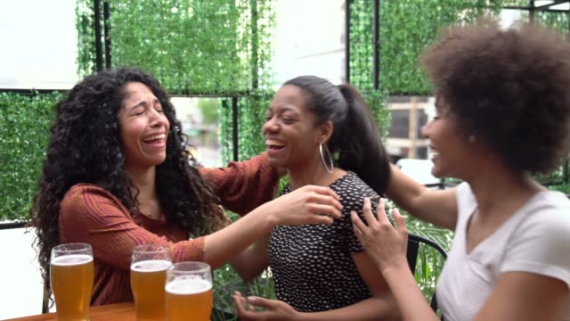 black woman telling her friends good news while they hug and toast with beer - congratulating stock videos and b-roll footage