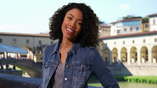 black woman tourist on vacation in venice laughing and smiling by ponte vecchio - ponte点の映像素材/bロール