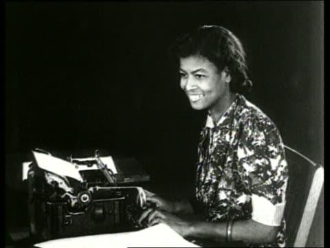 vídeos y material grabado en eventos de stock de b/w black woman typing on typewriter and smiling / sound - secretaria