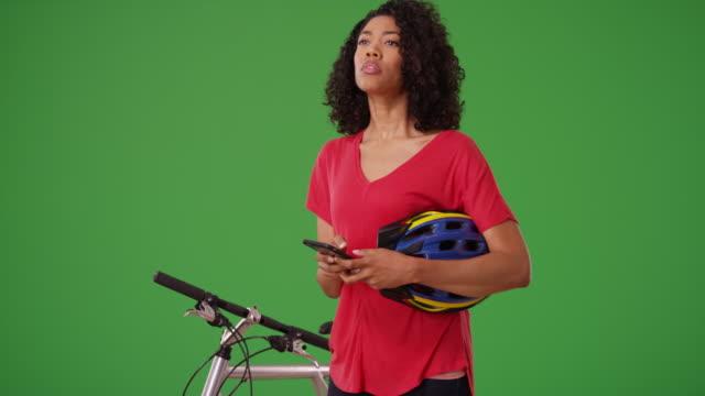 black woman using smartphone map app to find bike route or text on green screen - 頭にかぶるもの点の映像素材/bロール