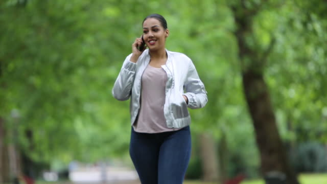 black woman walking in the park on her mobile phone - battersea stock videos & royalty-free footage