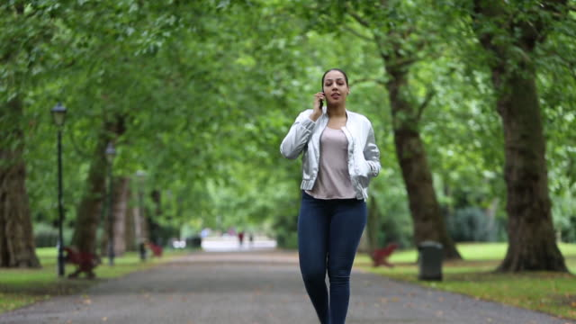 black woman walks and talks on her mobile phone - battersea stock videos & royalty-free footage