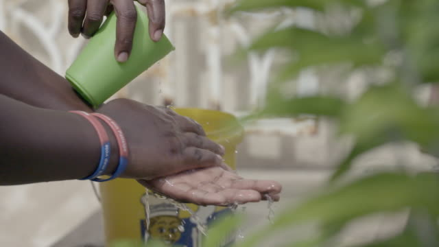 Black woman washing hands with water cup