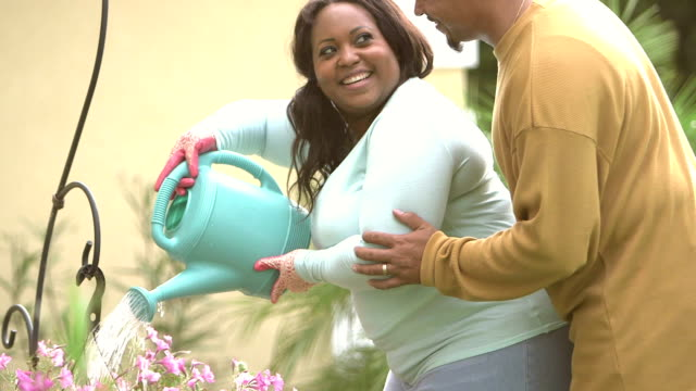 Black woman watering flowers, husband joins her