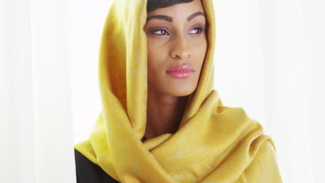 black woman wearing gold head scarf by bright window - traditional clothing stock videos & royalty-free footage