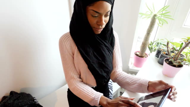 black woman with headscarf working on her ipad indoor - succulent plant stock videos & royalty-free footage