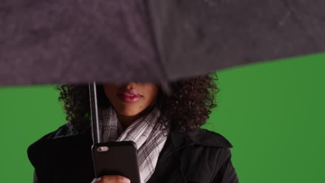 black woman with red lips under umbrella texting on phone in rain on greenscreen - ビジカジ点の映像素材/bロール