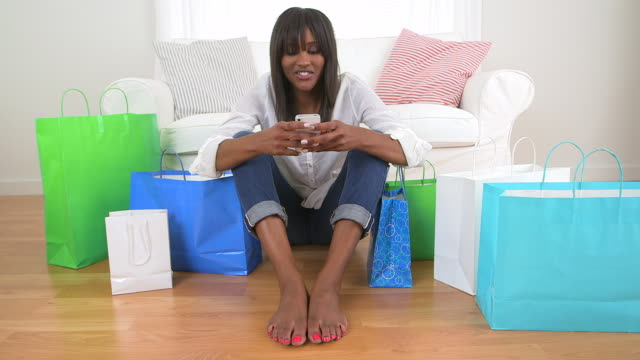 Black woman with shopping bags texting on cell phone