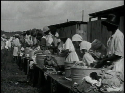 Black women doing laundry with washboards in tubs / Baton Rouge Louisiana United States