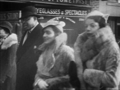 B/W 1930 PAN Black women in fur coats + matching hats walking on Harlem sidewalk / NYC / newsreel