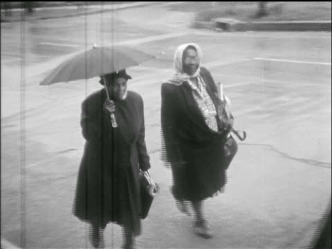 black women walking on sidewalk past camera / montgomery bus boycott, al / newsreel - アメリカ公民権運動点の映像素材/bロール