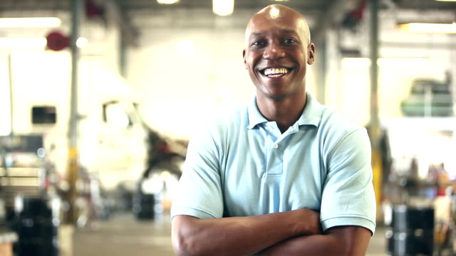 Black worker in trucking industry, smiling at camera