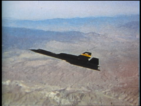 1973 aerial black yf-12 reconnaisance jet flying over mountains (prototype for sr-71 blackbird) - military airplane stock videos & royalty-free footage