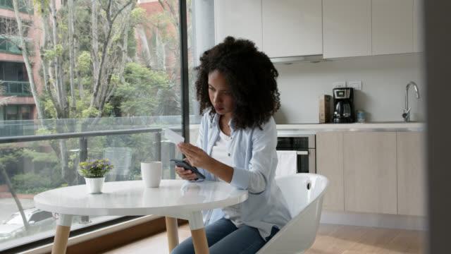 vídeos y material grabado en eventos de stock de mujer joven negra en casa haciendo banca en línea usando teléfono inteligente y tarjeta de crédito mientras bebe café - afro