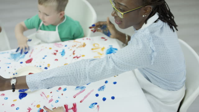 Black Young Woman Instructing a Finger Painting Class