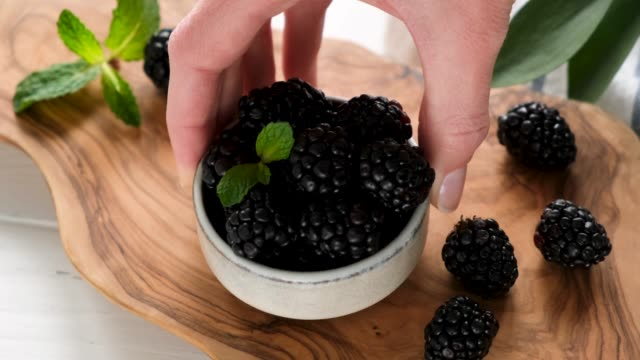 blackberries in bowl on wooden board - picking up stock-videos und b-roll-filmmaterial
