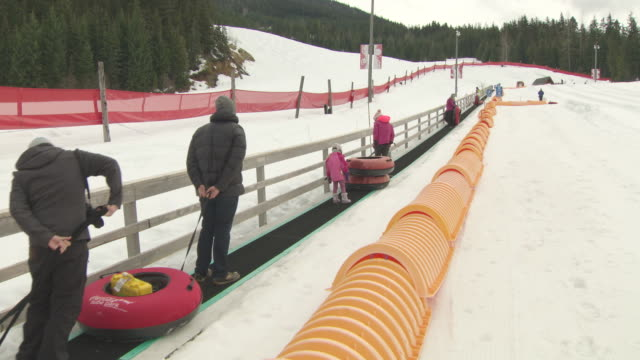 blackcomb ski resort anonymous people standing on an automatic conveyer belt holding rubber tubes while being pulled to the top of the slope / people... - rubber ring stock videos & royalty-free footage