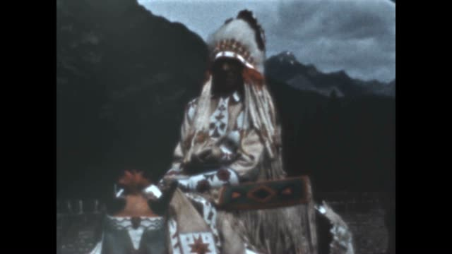blackfoot indians parade down banff avenue with chief joe calf child in attendance from a home movie archive - ネイティブアメリカン点の映像素材/bロール
