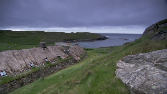 a blackhouse overlooks an inlet. available in hd. - isole ebridi video stock e b–roll