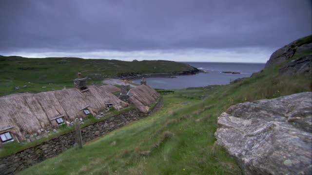 vídeos de stock e filmes b-roll de a blackhouse overlooks an inlet. available in hd. - telhado de palha