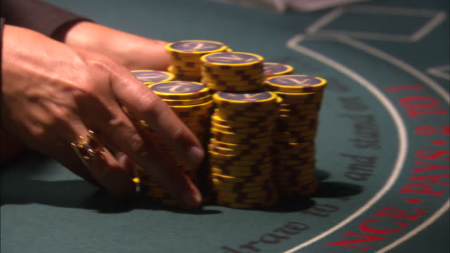 a blackjack dealer passes stacks of chips to a player who runs his hands through the stack creating a pile on the table. - gambling chip stock videos and b-roll footage