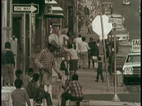 pan blacks hanging out and walking on sidewalk in innercity philadelphia / united states - philadelphia pennsylvania video stock e b–roll