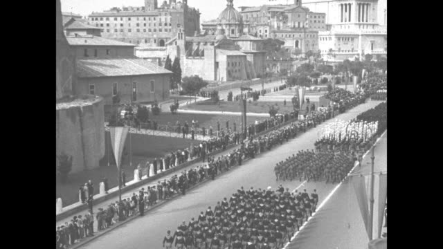vs blackshirts bearing standards with eagle at the top / elevation shot fascist troops bearing standards and flags march past the colosseum /... - piazza venezia stock videos and b-roll footage