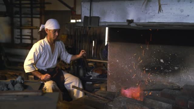 blacksmith adding coal to the furnace - fuoco acceso video stock e b–roll