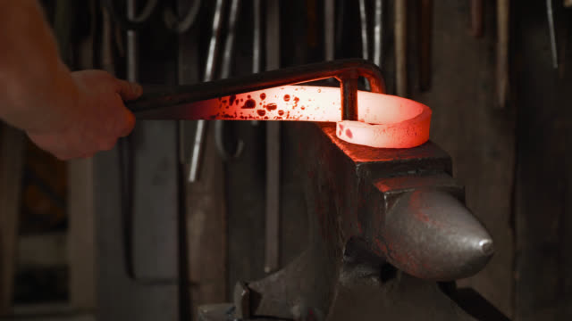 vídeos de stock e filmes b-roll de blacksmith bends metal bar with wrench on anvil - ferro metal