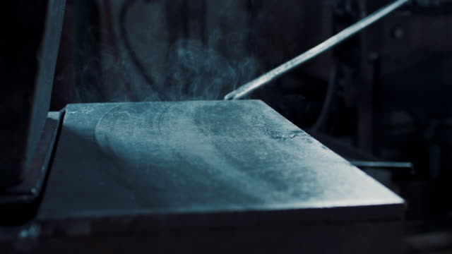 Blacksmith cleaning forging press