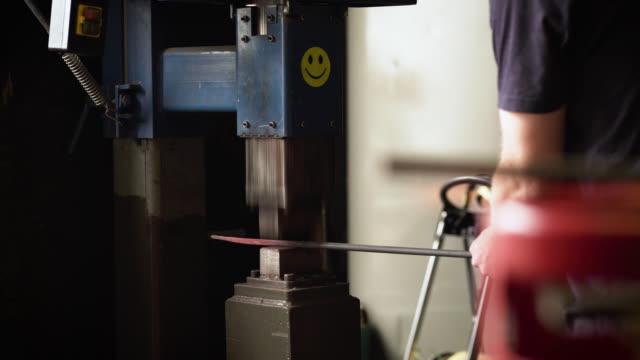 vídeos de stock e filmes b-roll de blacksmith forges metal with power hammer - ferro metal
