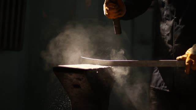 blacksmith forging a iron bar on anvil block - sledgehammer stock videos & royalty-free footage